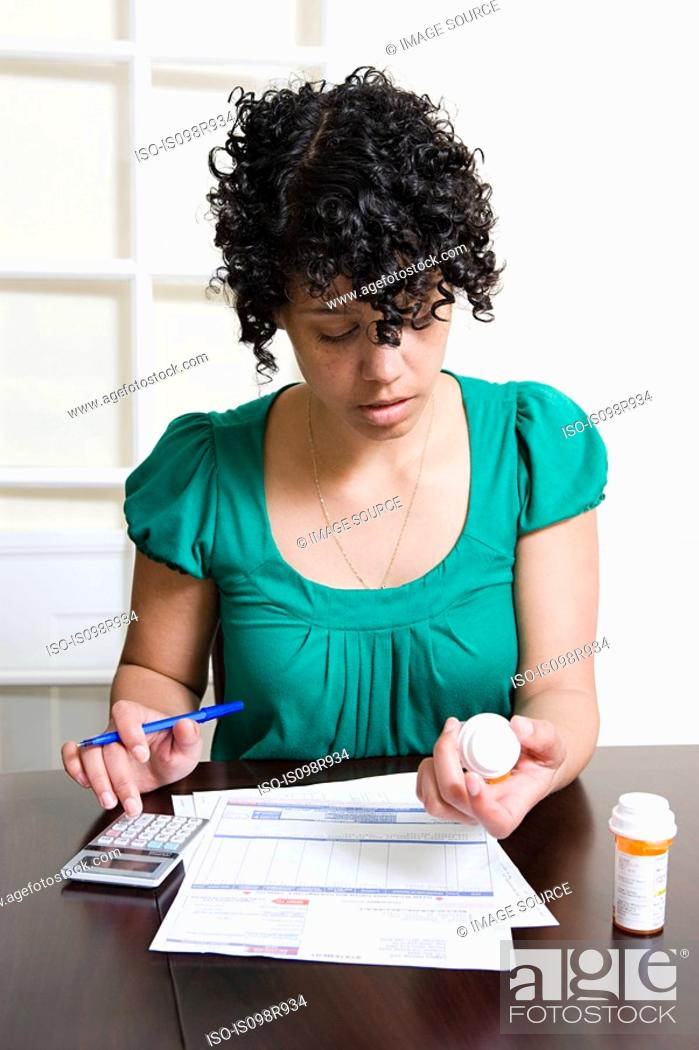 Stock Photo: Woman with bills and tablets using calculator.