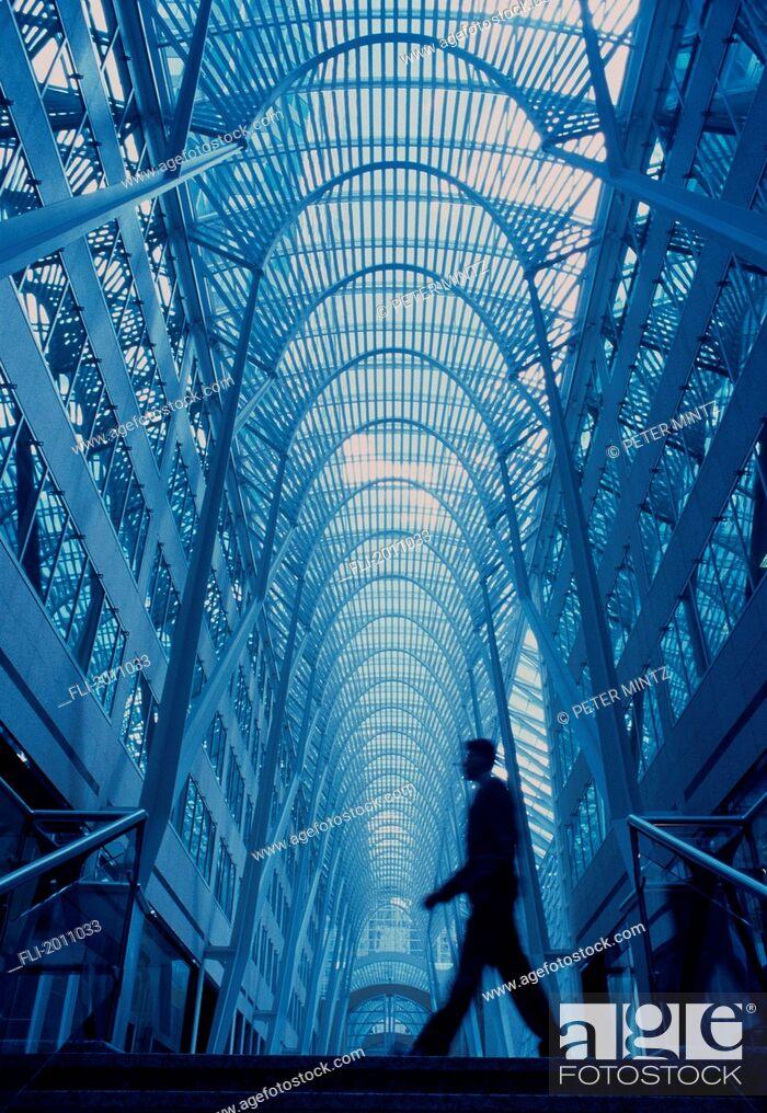 Imagen: Fv3369, Peter Mintz; Underview, Businessman Walking Through Glass Atrium.