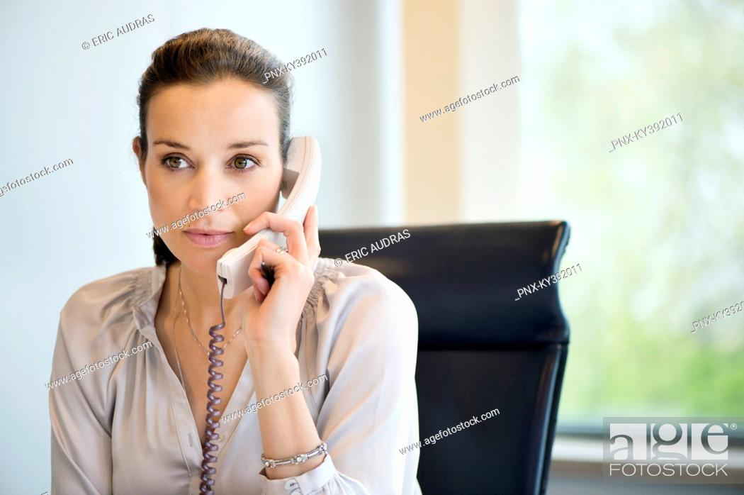 Stock Photo: Businesswoman talking on a landline phone in an office.