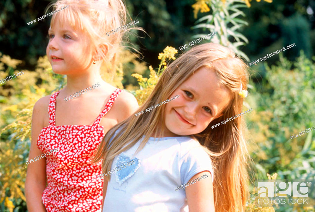 Stock Photo: Portrait of two young girls standing in a garden.