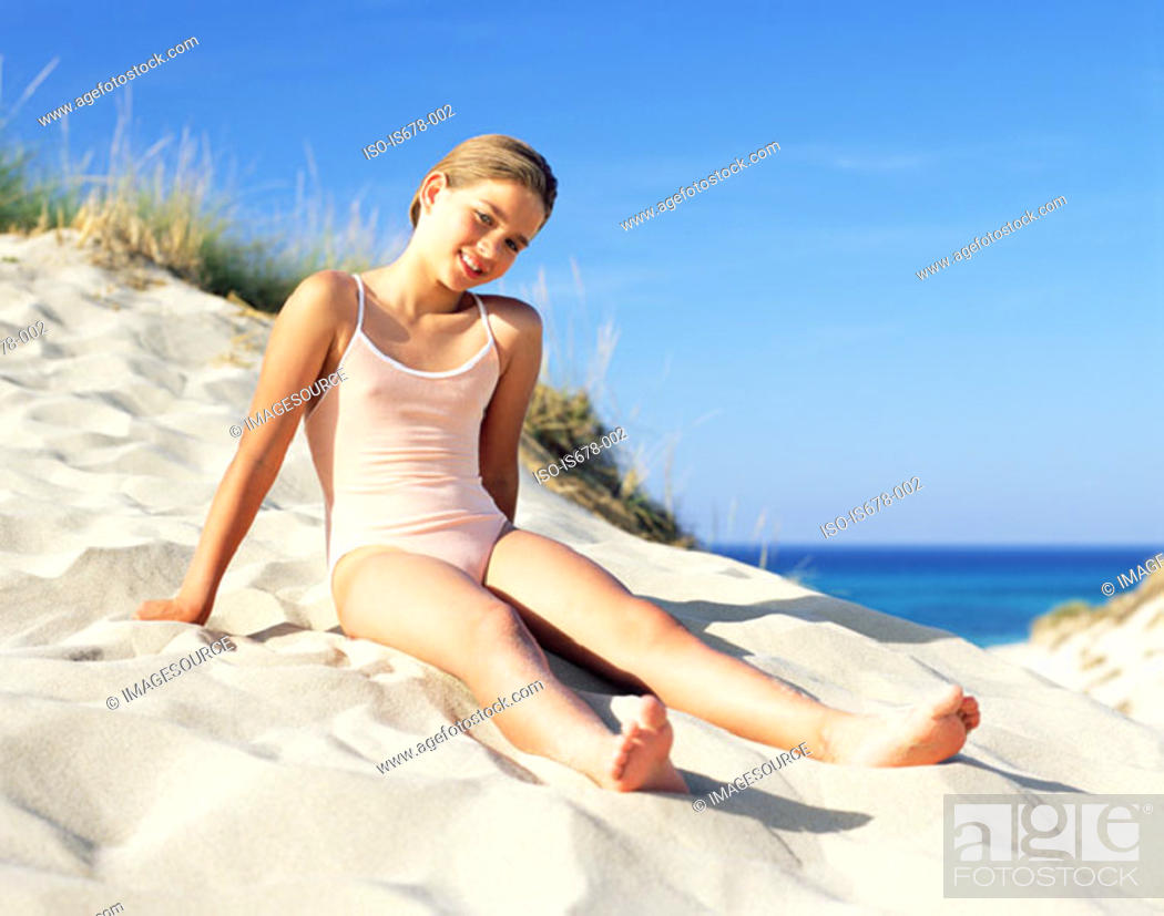 Stock Photo: Girl sitting on a sand dune.
