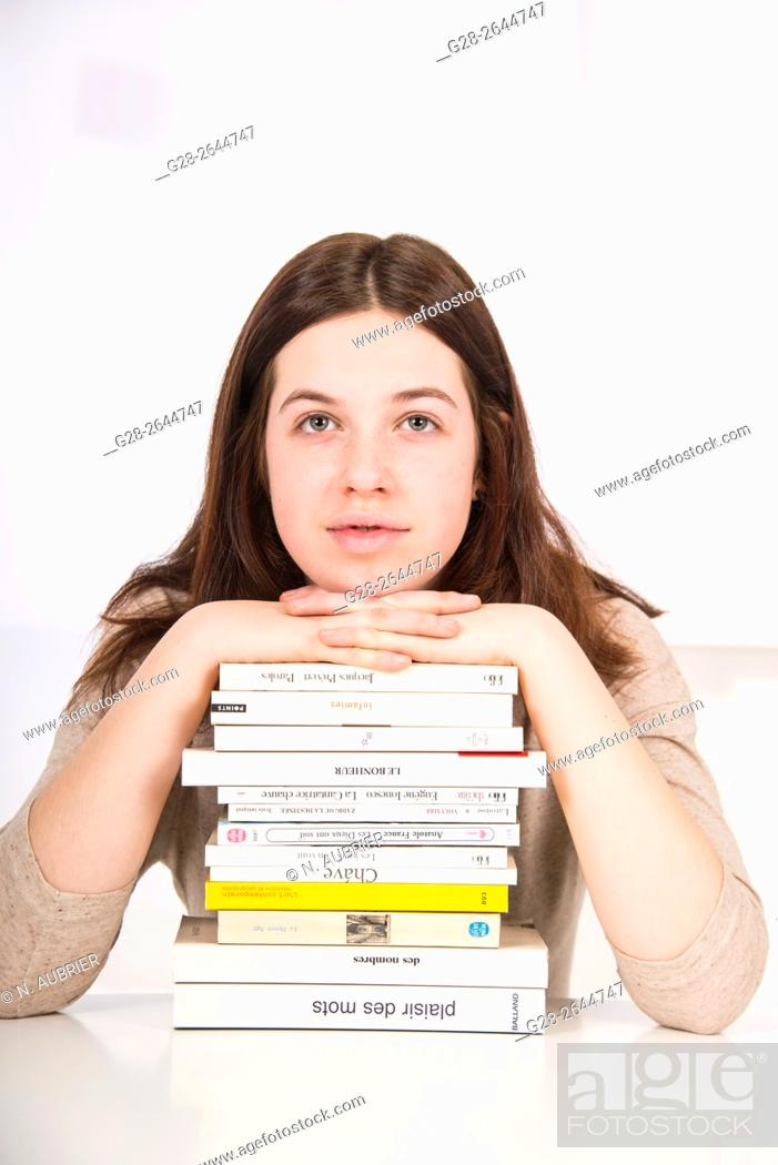 Stock Photo: Teenage girl thinking over pile of books, overworked.