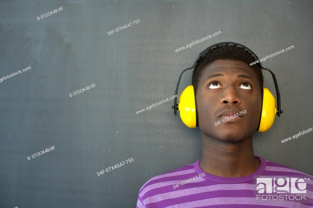 Stock Photo: Student wearing ear protection leaning against blackboard.