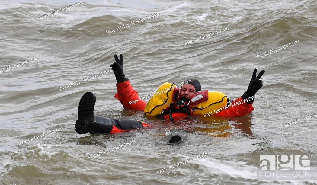 Stock Photo: Actor Till Demtroeder, new embassador of the German Maritime Search and Rescue Service (DGzRS) waves in the water wearing a survival suit in Cuxhaven, Germany.