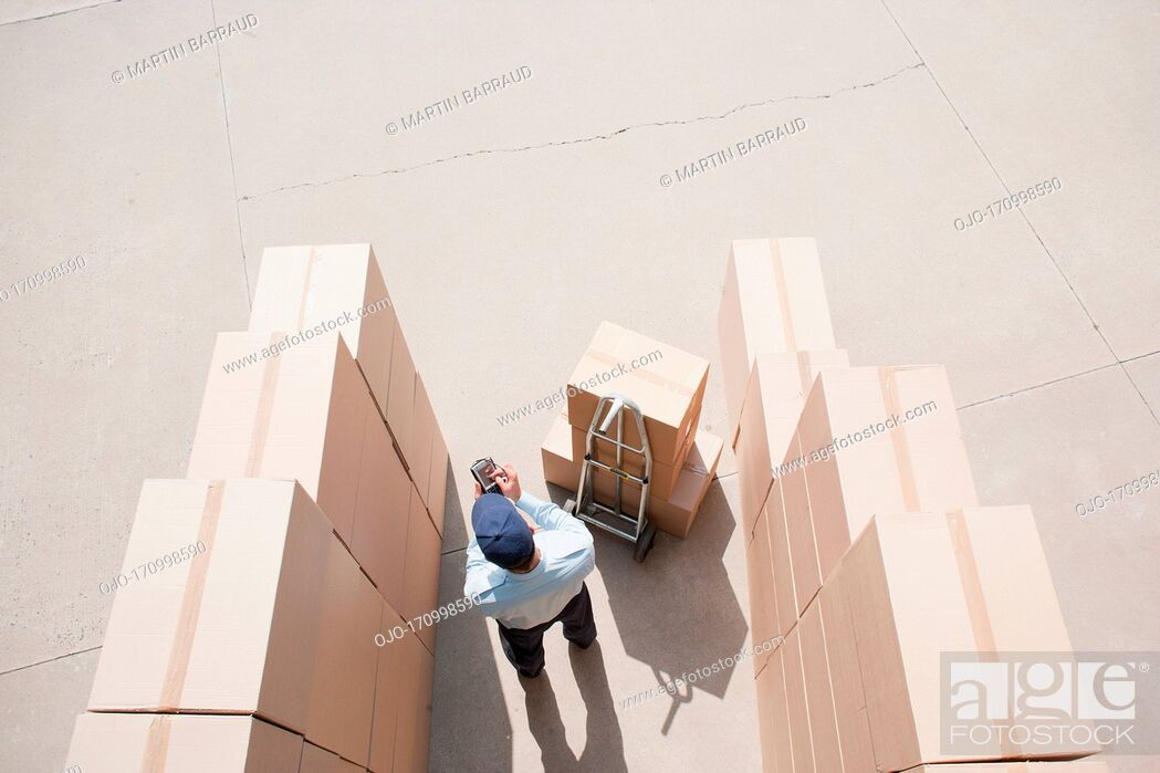 Stock Photo: Worker standing with boxes and hand truck.
