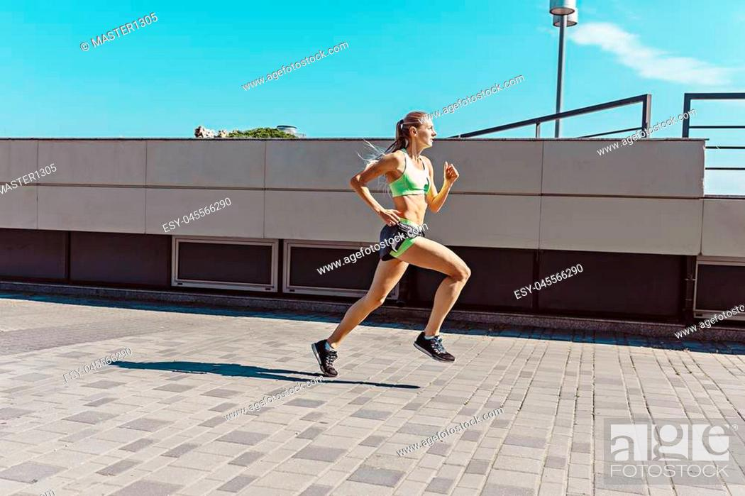 Stock Photo: Pretty sporty woman jogging at city at morning. Fit fitness young caucasian girl running. Female sports model in summer sunny day exercising outdoor.