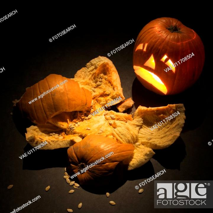 Stock Photo: Upset jack-o'-lantern looking at smashed pumpkin.
