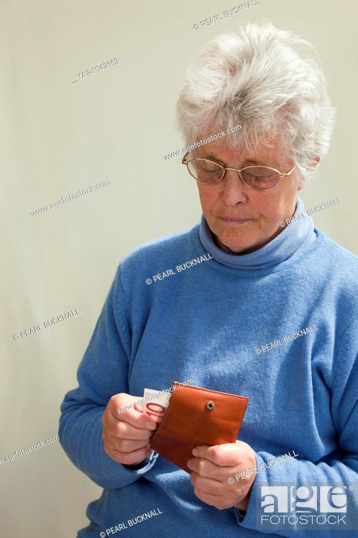 Stock Photo: Europe  Senior woman pulling ten Euro note from a purse looking worried MR 09/05.