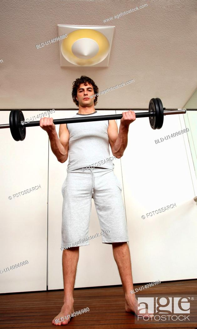 Stock Photo: Young man lifting weights.