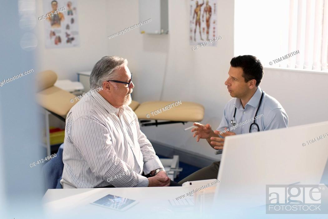 Stock Photo: Male doctor talking with patient in doctors office.