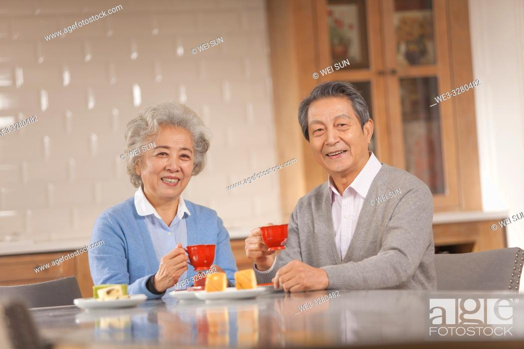 Imagen: Happy old couple drinking tea in the kitchen, Chinese ethnicity.