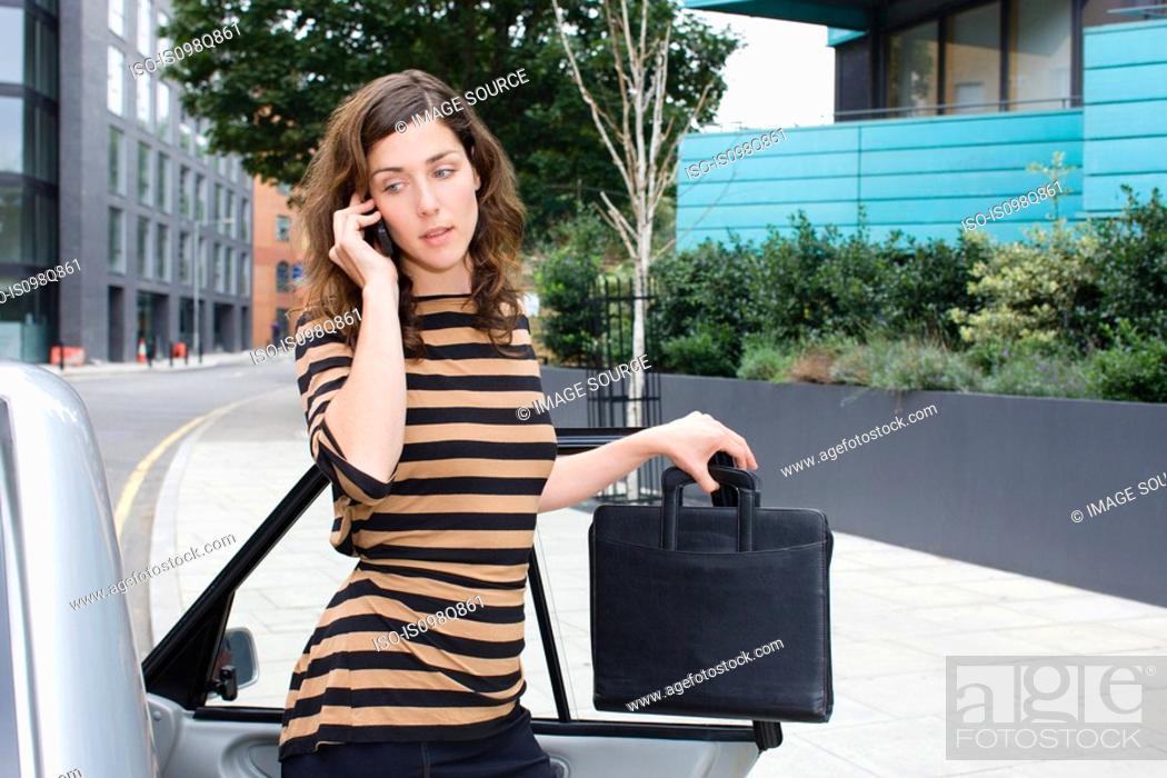 Stock Photo: Woman on cellphone by car.