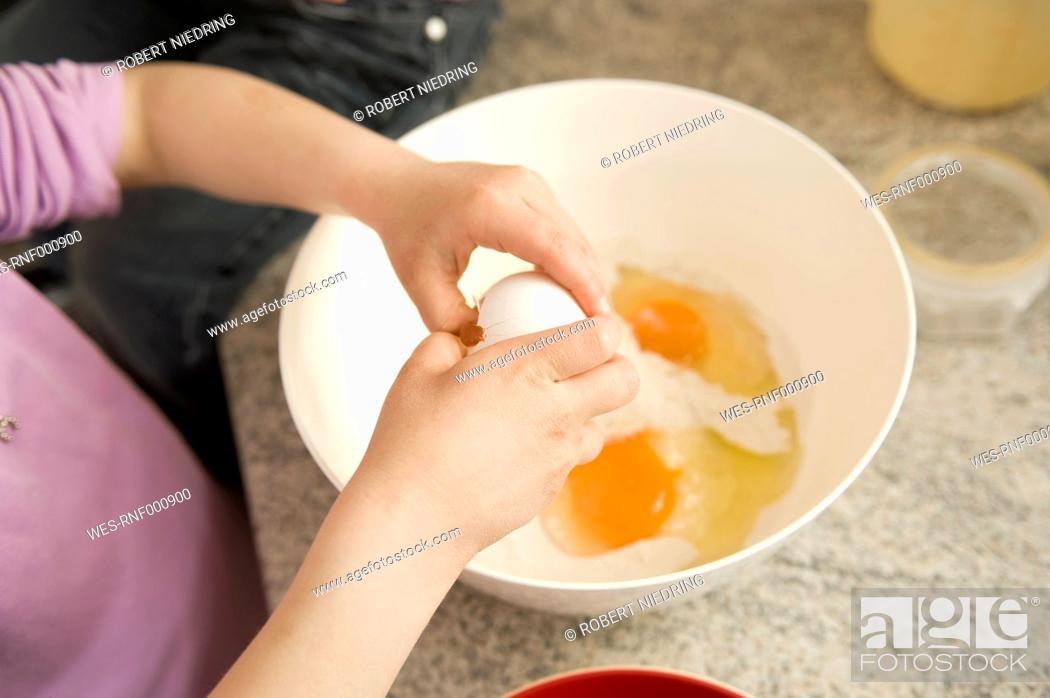 Stock Photo: Girl breaking egg in bowl.