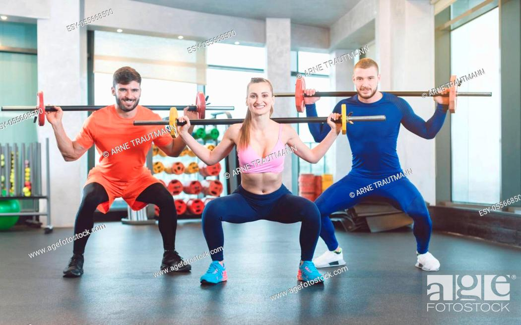 Stock Photo: Group of fit young people doing weight exercise in a modern gym.