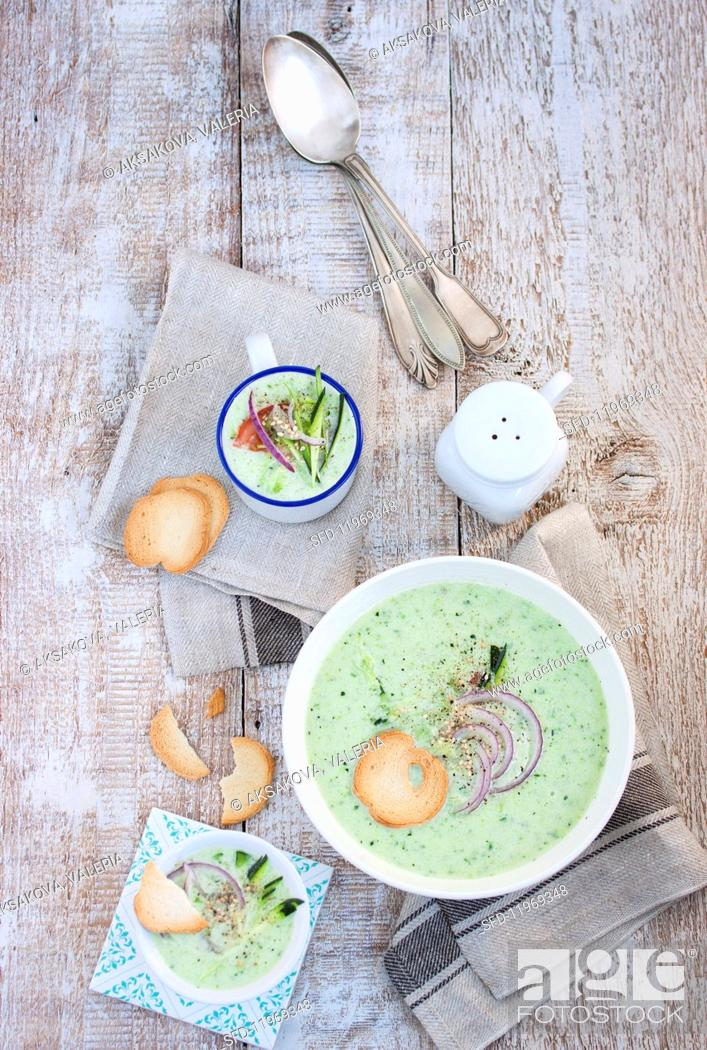 Stock Photo: Cold courgette and cucumber soup with bread chips (seen from above).