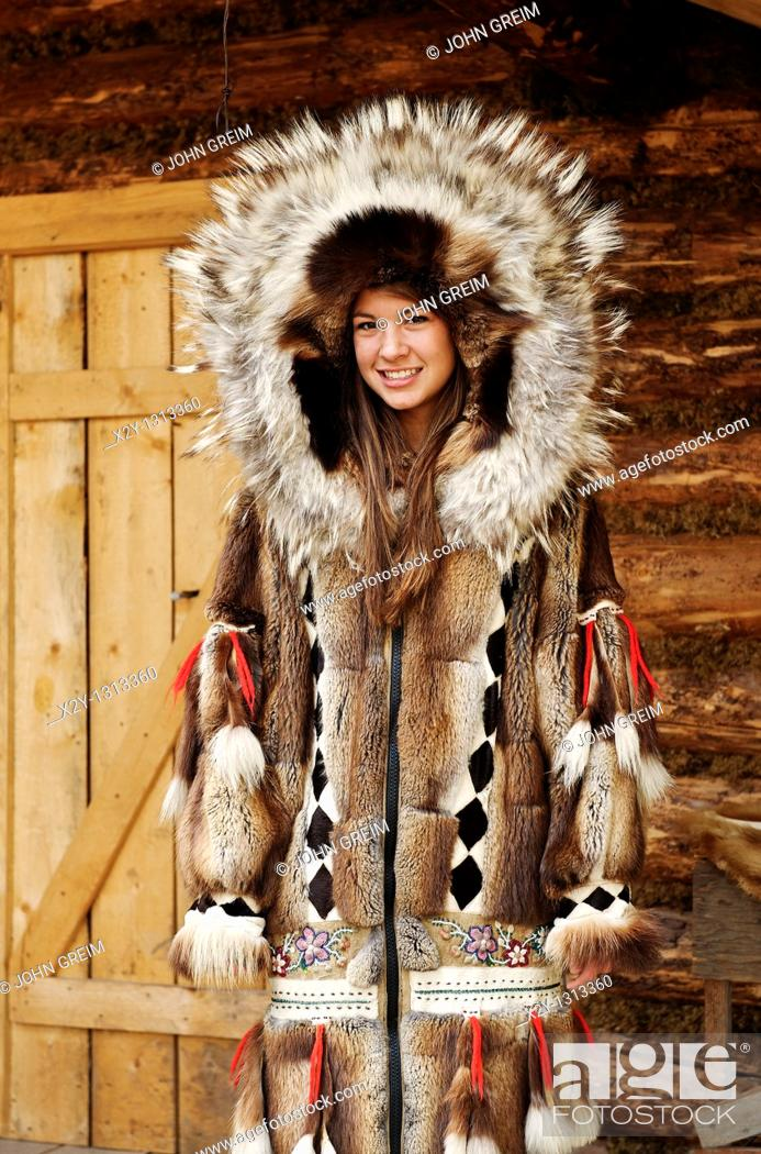 Stock Photo: Young Athabascan woman modeling the traditional fur clothing of her native tribe, Chena Indian village, Alaska.