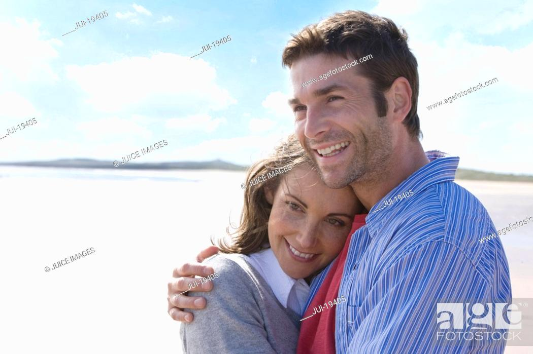 Stock Photo: Mid adult couple embracing on beach.