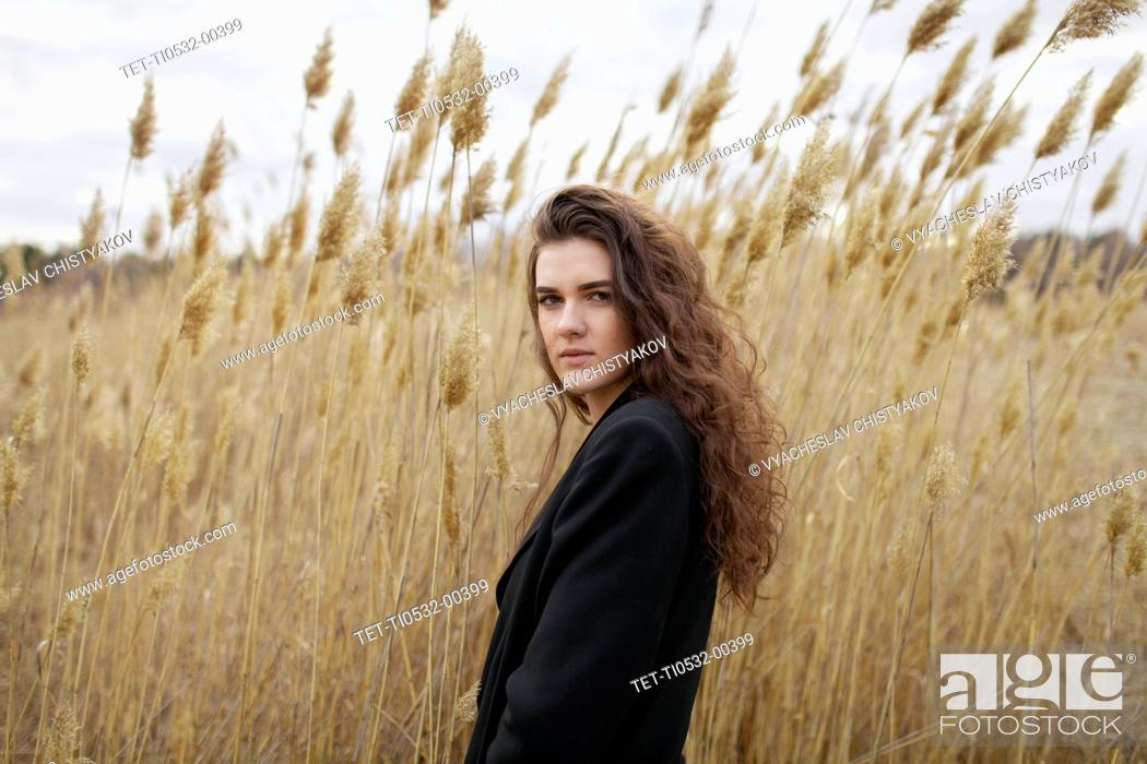 Stock Photo: Russia, Omsk, Portrait of young woman in tall grass.