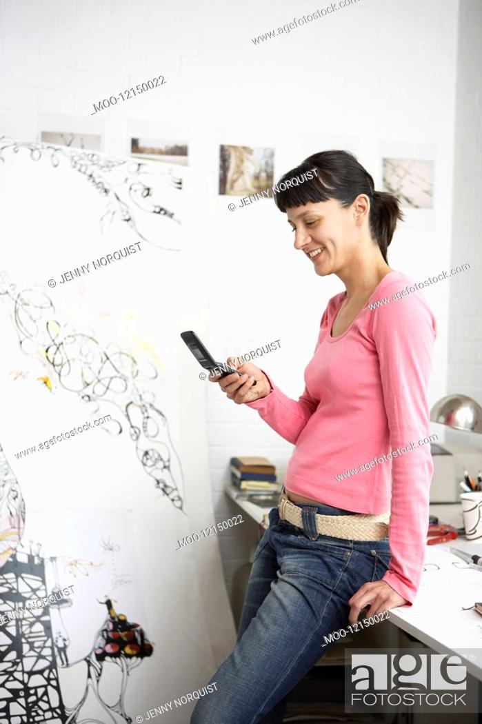 Stock Photo: Smiling woman using cell phone leaning on desk.