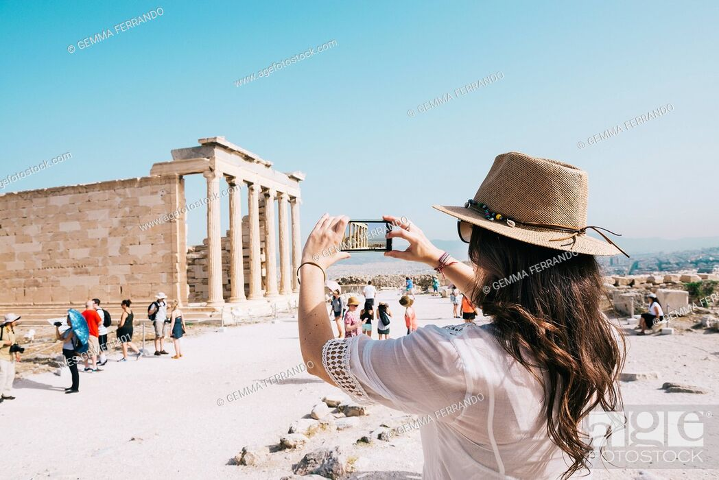 Imagen: Greece, Athens, woman taking a cell phone picture of the Erechtheion temple in the Acropolis.