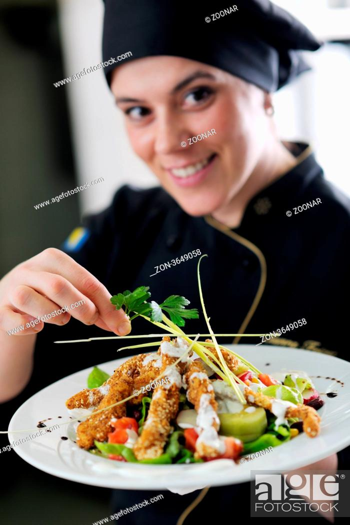 Stock Photo: beautiful young chef woman prepare and decorating tasty food in kitchen.