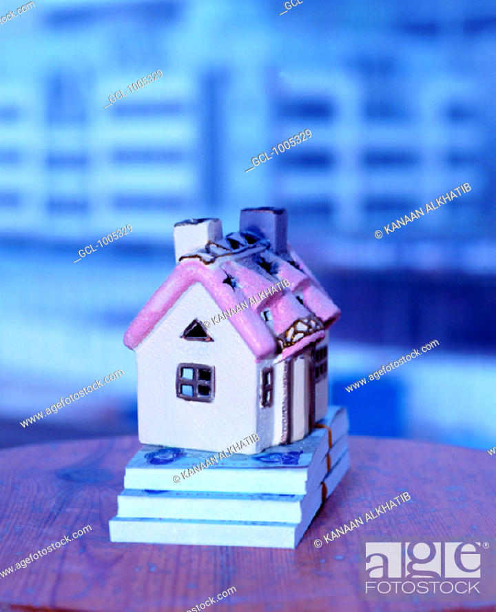 Stock Photo: Toy house on top of pile of UAE money.