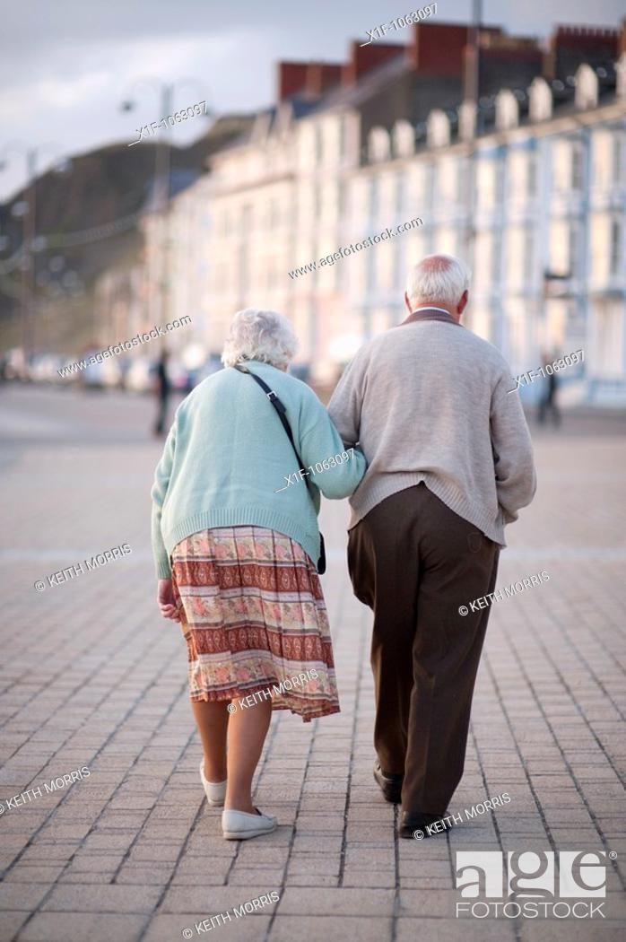 Stock Photo: Elderly couple, old man and woman, walking in Aberystwyth promenade, summer evening, Wales UK.