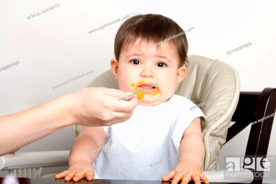 Stock Photo: Cute baby infant boy girl expresses dislike disgust for food fed by spoon.