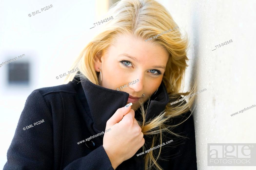 Stock Photo: Young woman portrait in Black coat, it's cold and windy.