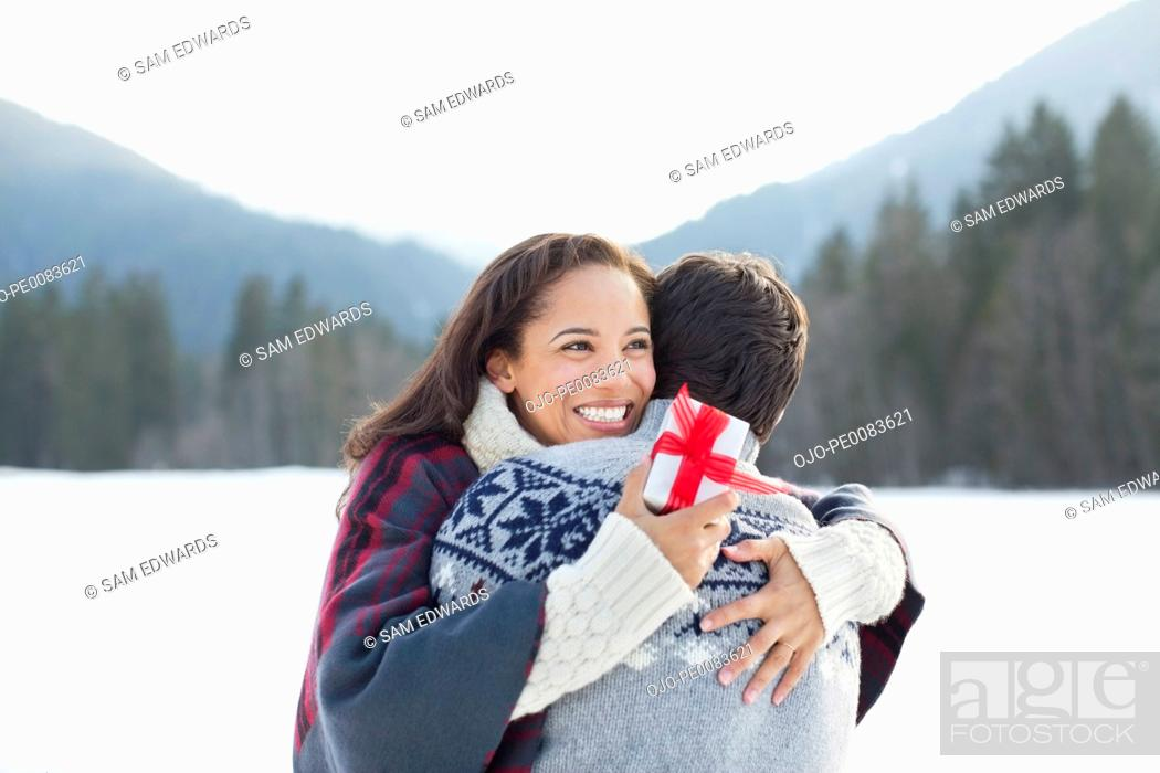 Stock Photo: Smiling woman holding Christmas gift and hugging man in snow.