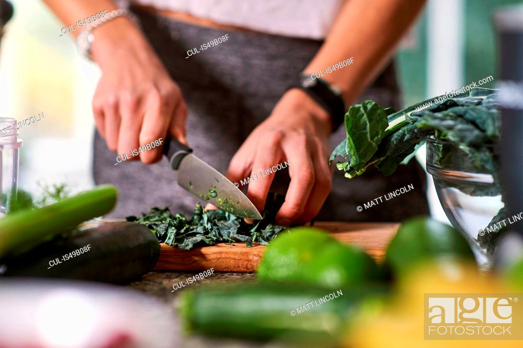 Stock Photo: Hands of young woman slicing cabbage at kitchen table.