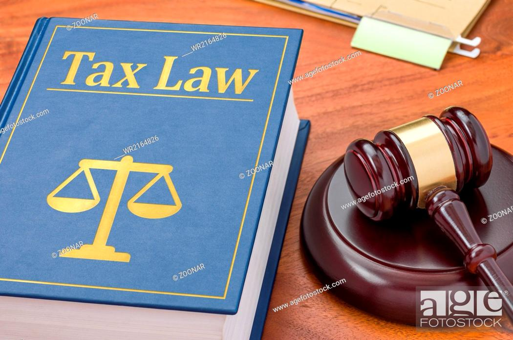 Stock Photo: A law book with a gavel - Tax law.