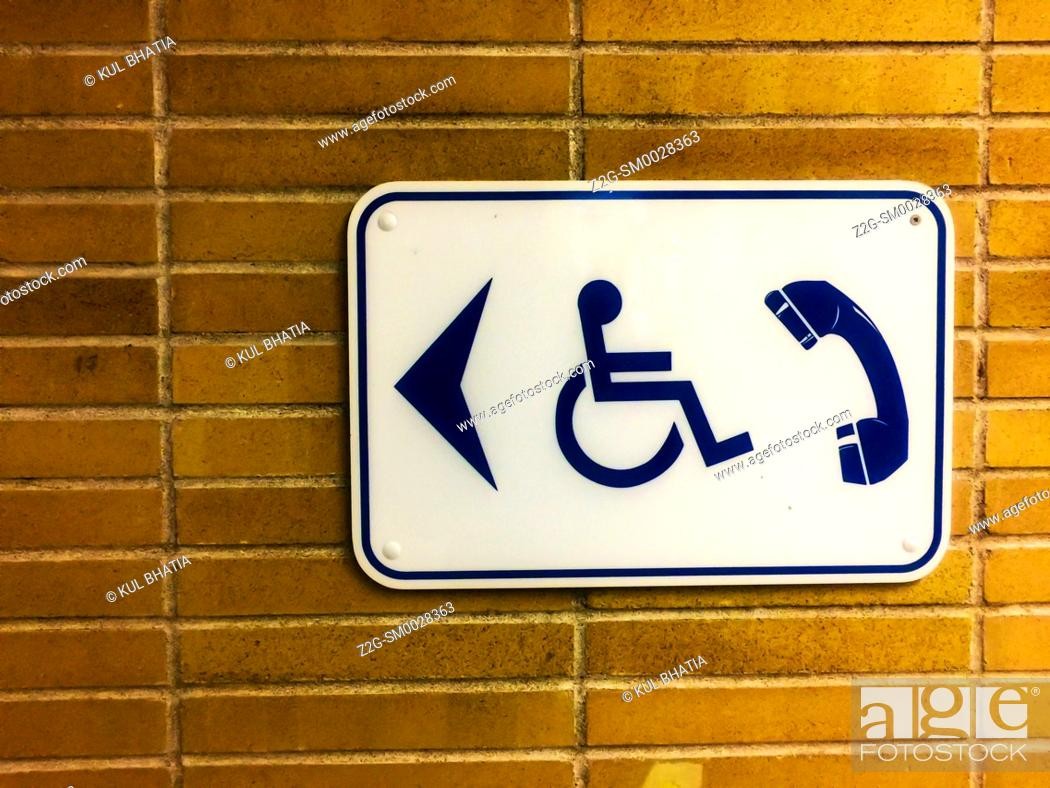 Stock Photo: Pay phone accessible to handicapped users, Sign on a brick wall, Canada.