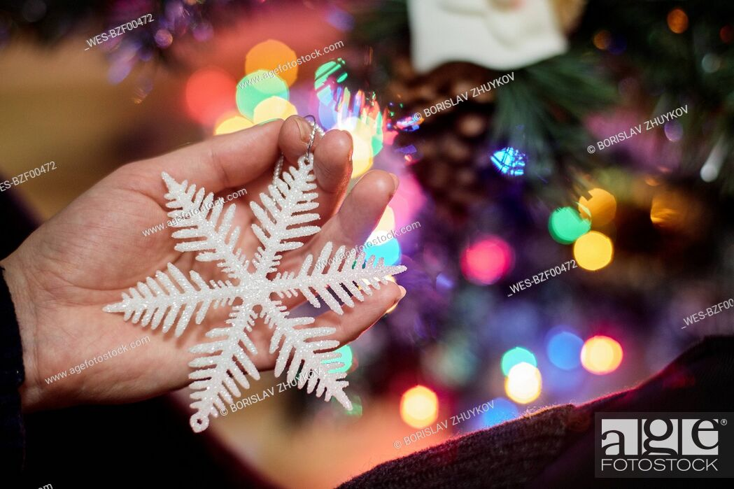 Stock Photo: Woman's hand holding Christmas ornament, close-up.