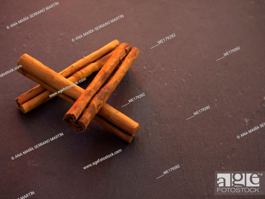 Imagen: Several dried cinnamon sticks on a slate plate.