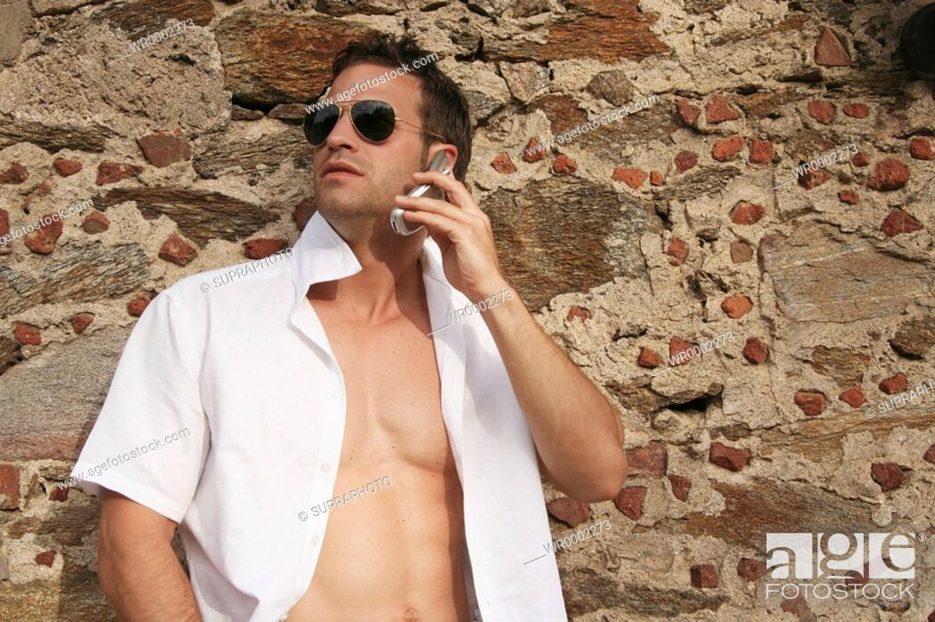 Stock Photo: Dark Hair, Cell Phone, Color Image, Man, Outdoors, People, Summer, View, Sunglasses, Alone, Object, White, Spring, Wall, Old, Place, Stone, Communication, Telephone, Position, Shirt, Year, Calling, Season, Seduction, Clothing, Front, Connotation, Bare Chested
