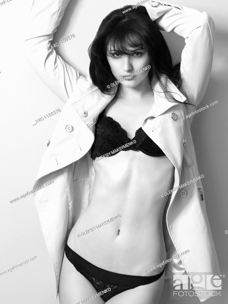 Stock Photo: Young beautiful woman in lingerie under a trench.