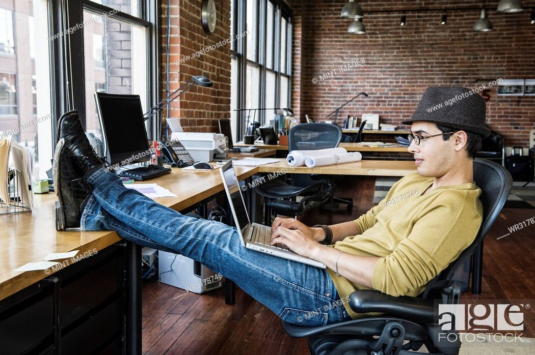 Stock Photo: Hispanic man working on his laptop computer at this creative office work station.