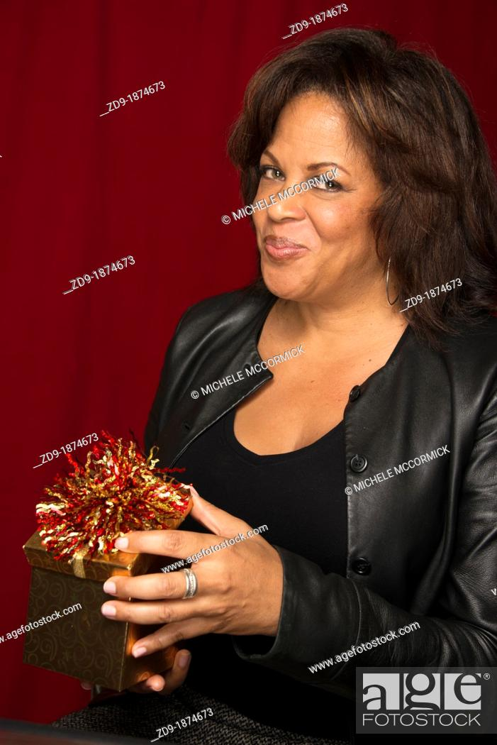 Stock Photo: A beautiful middle-aged black woman opens a gift box with a wry grin.