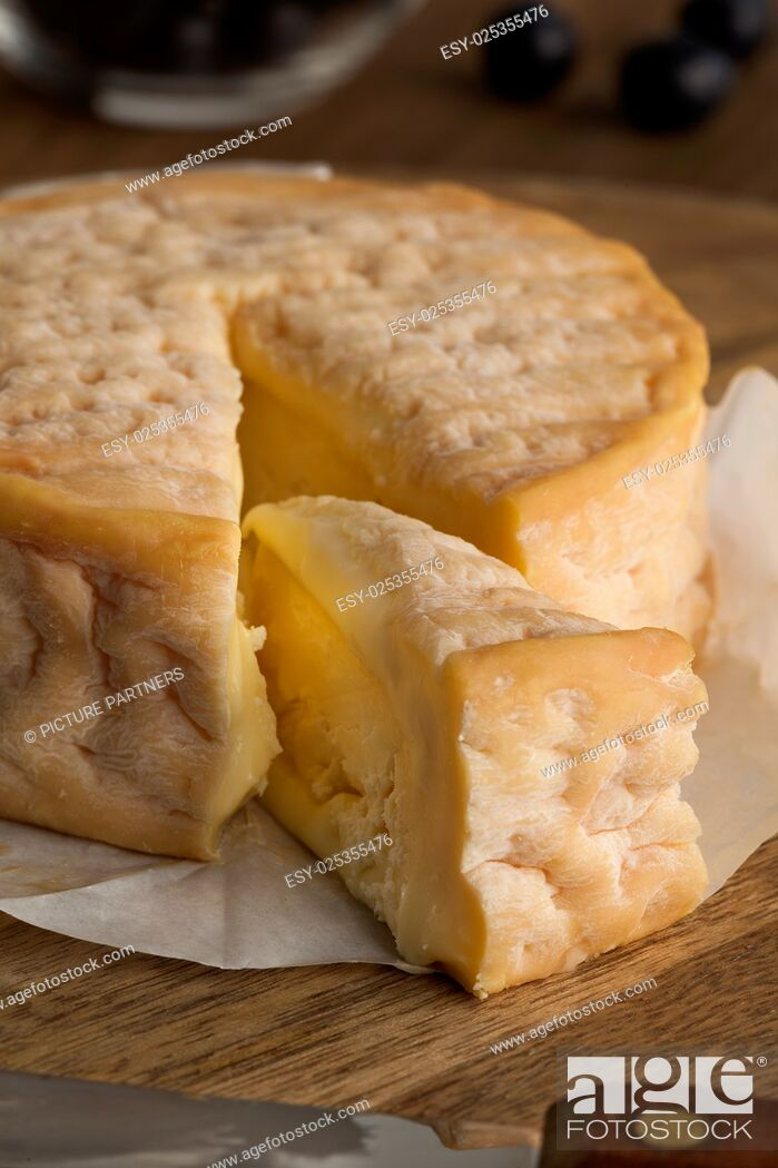 Stock Photo: Creamy ripe Epoisses cheese and wedge close up.