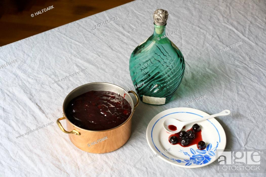 Stock Photo: High angle view of blueberry syrup in pot with plate and bottle on tablecloth.