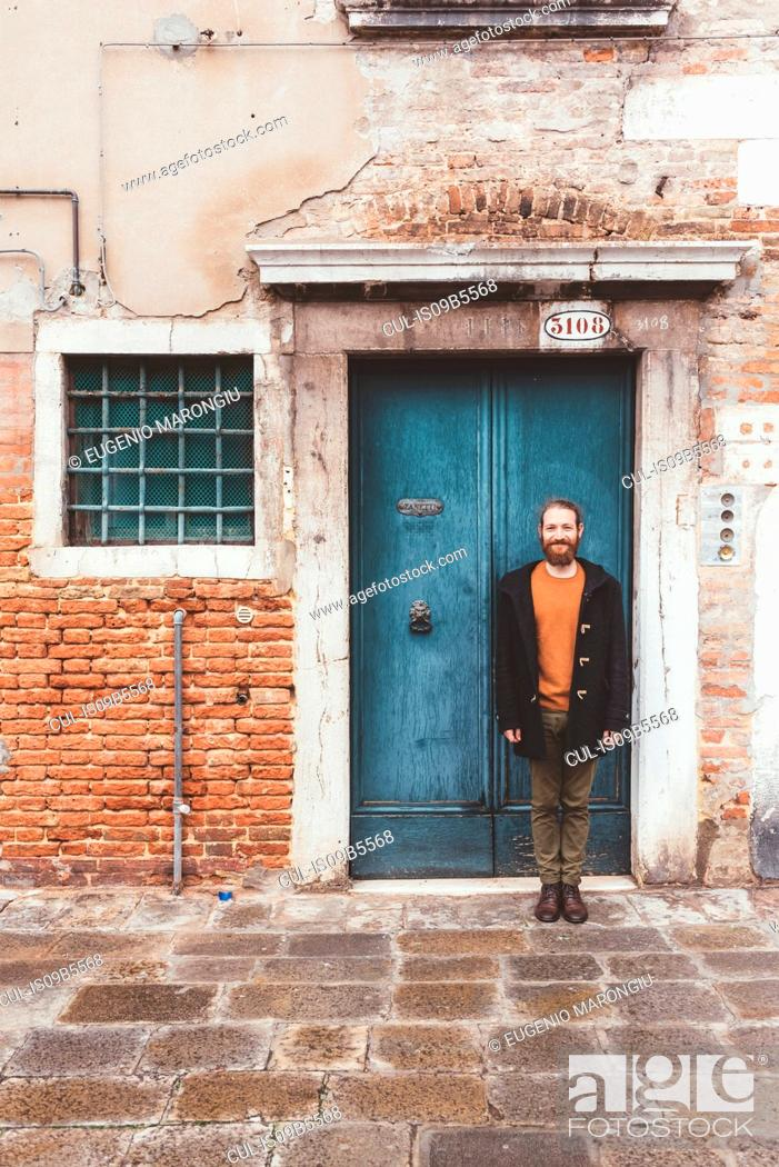 Stock Photo: Portrait of bearded mid adult man standing in front of old doorway, Venice, Italy.