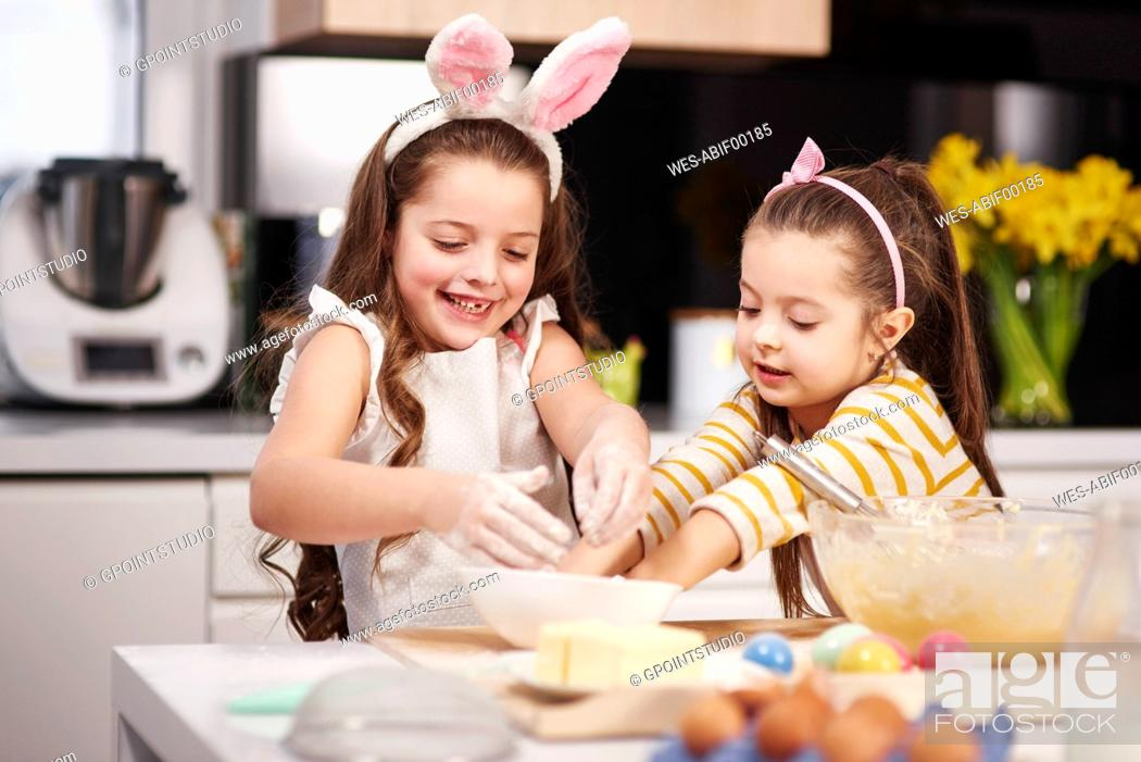 Stock Photo: Two sisters having fun baking Easter cookies in kitchen together.