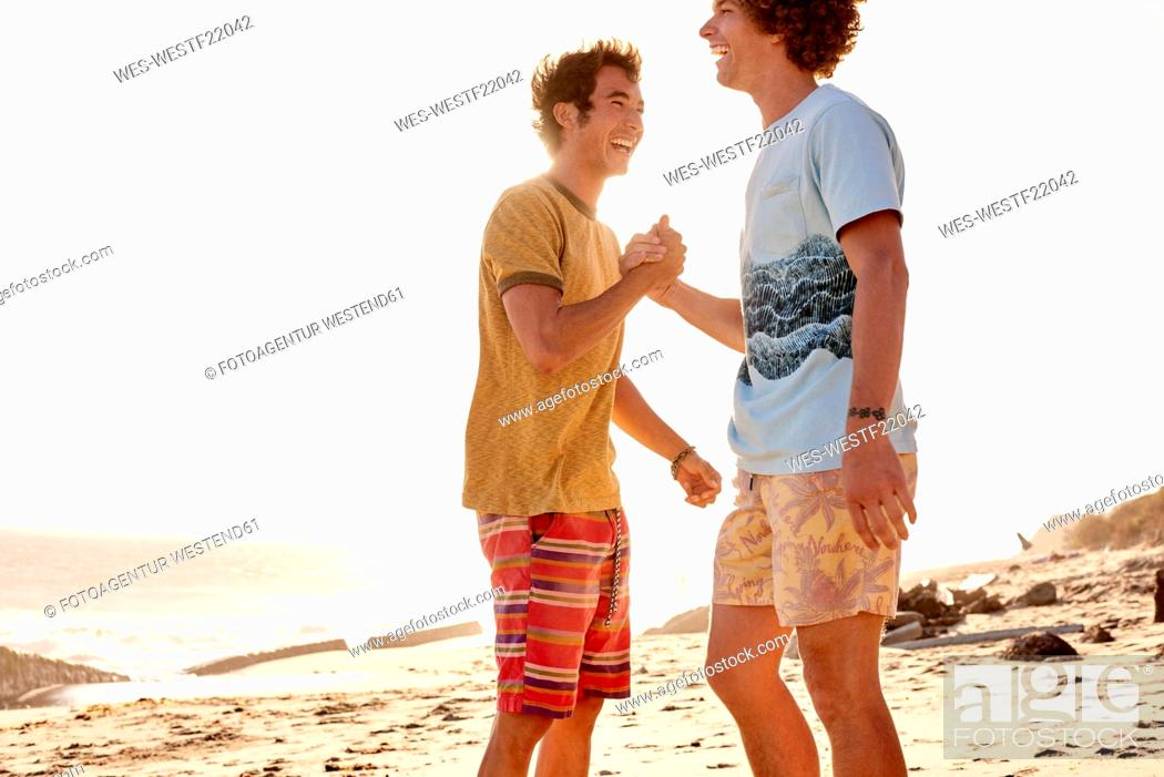 Photo de stock: Two happy young man on the beach.