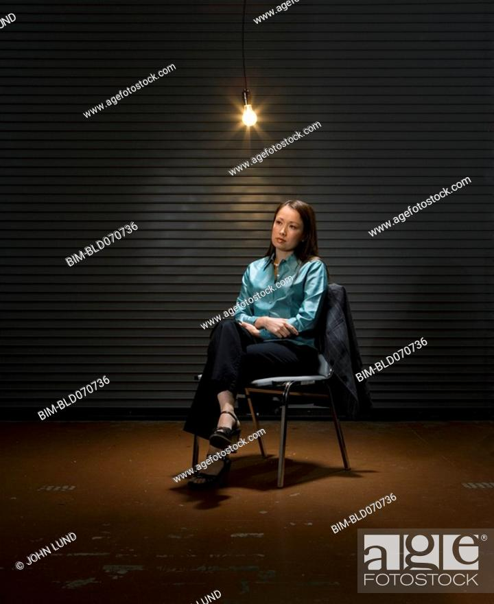 Stock Photo: Asian businesswoman sitting under light bulb.