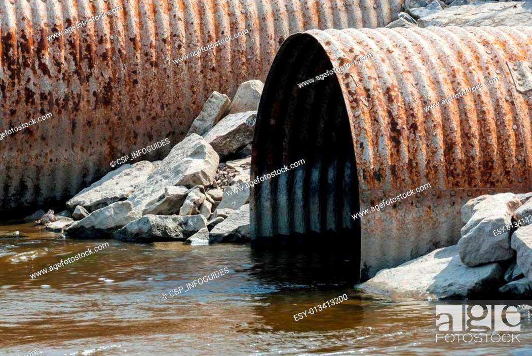 Stock Photo: Rusted culvert pipe opening in water.