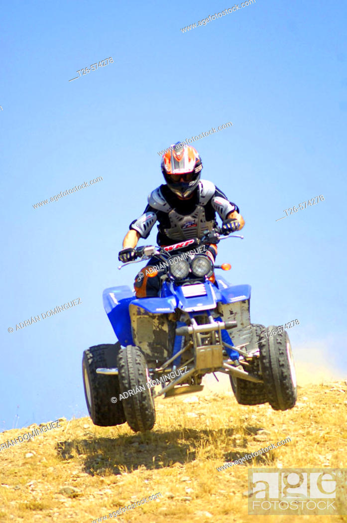 Stock Photo: Man driving a quad fast down the hill.