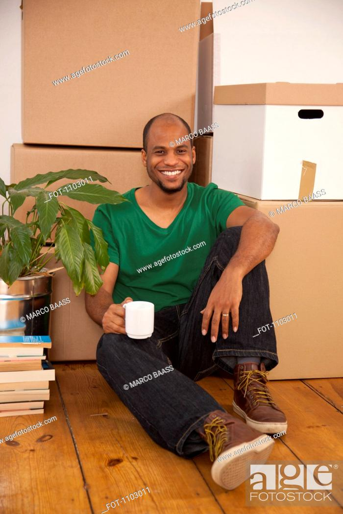 Stock Photo: A man taking a coffee break while moving house.