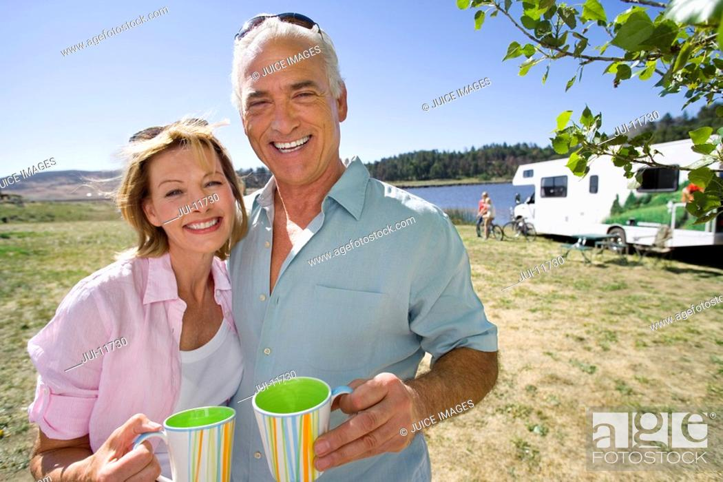 Stock Photo: Mature couple with mugs by motor home and lake, smiling, portrait.
