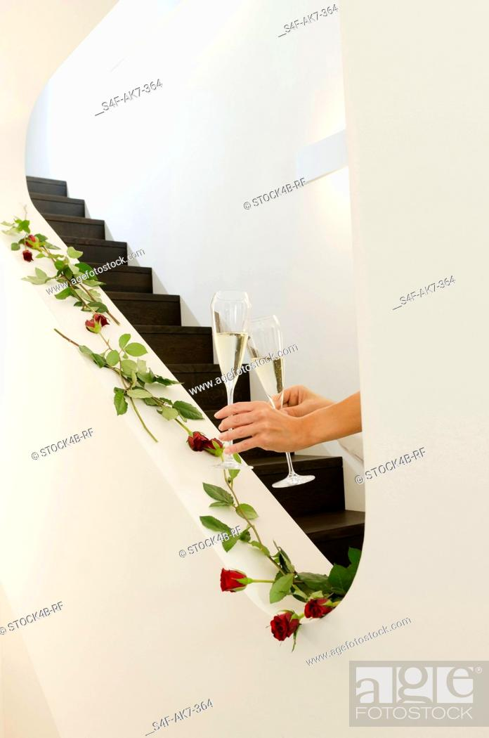 Stock Photo: Hands holding champagne glasses on staircase decorated with red roses.